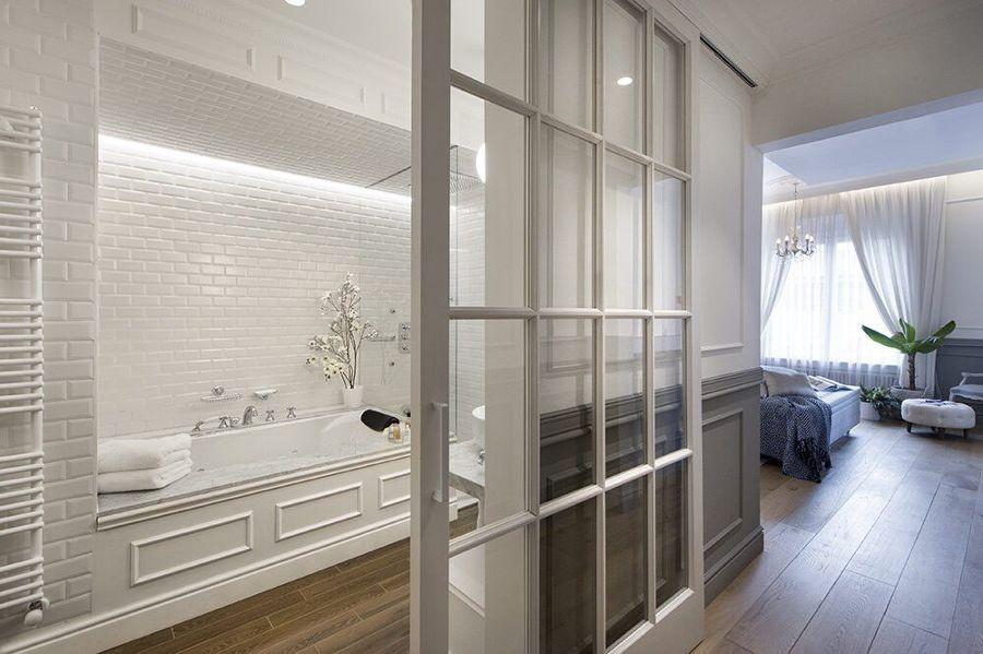 Baño en suite con puerta corredera de cristal con cuarterones de madera