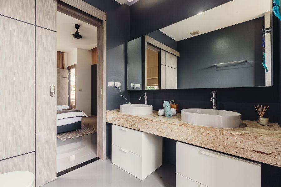Baño en suite con revestimientos en negro y encimera de mármol