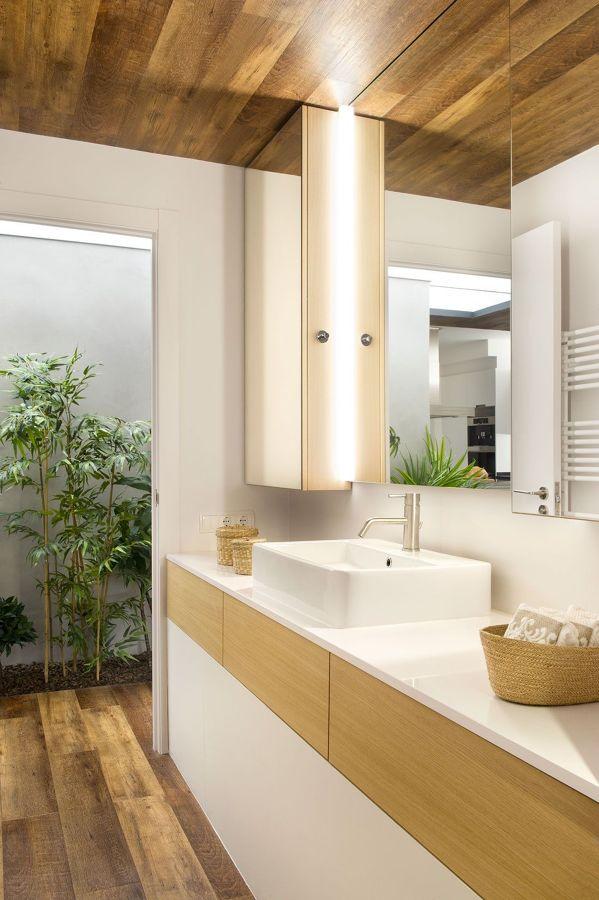 Baño funcional con techo de madera y plantas en patio interior