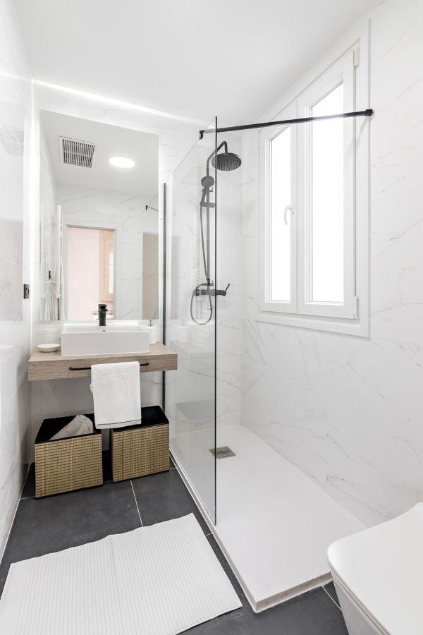 Baño minimalista en blanco y suelo gris