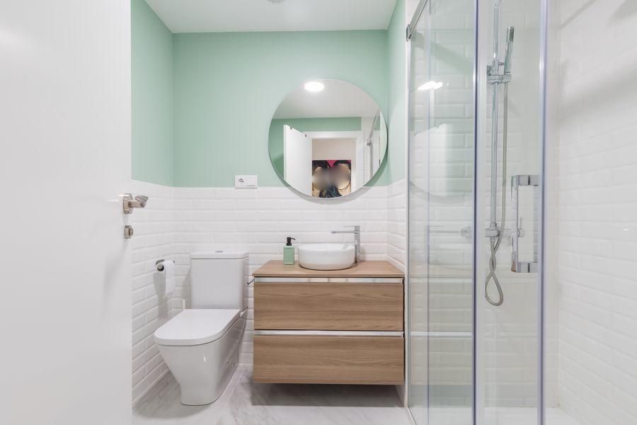 Baño moderno con azulejo tipo metro y lucido en verde.