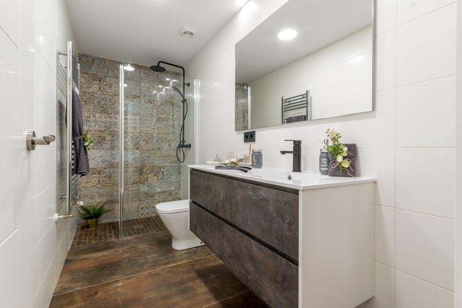 Baño reformado con ducha al fondo y revestimiento cerámico