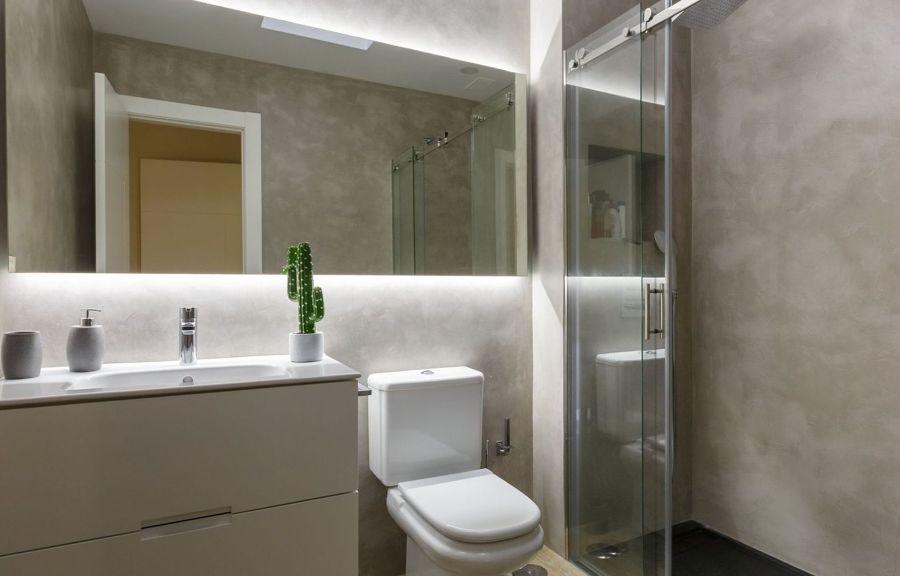 Baño revestido con microcemento y azulejo tipo madera en el suelo.