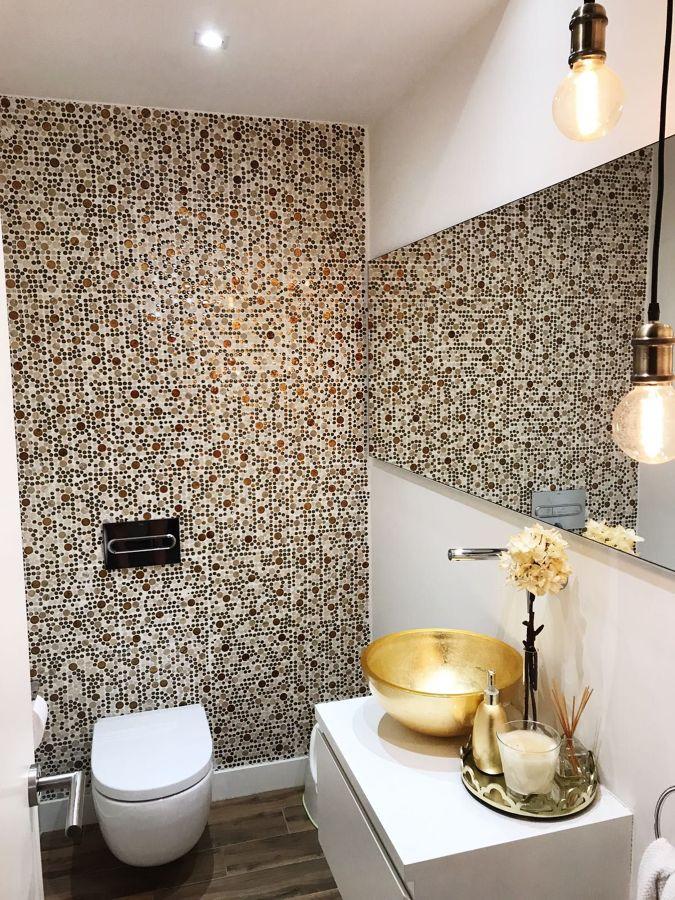 Baño sin ventana con gran espejo y lavabo dorado