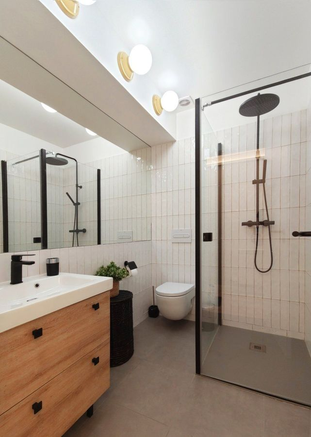 Baño sin ventanas con gran espejo y luz ambiental