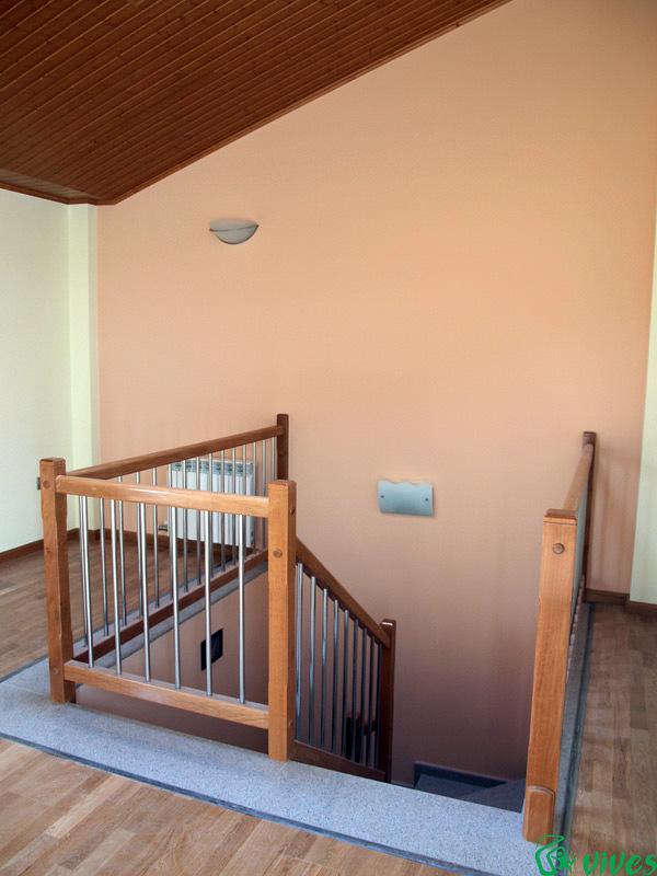 Buhardilla con escaleras de madera torneada y acero inoxidable