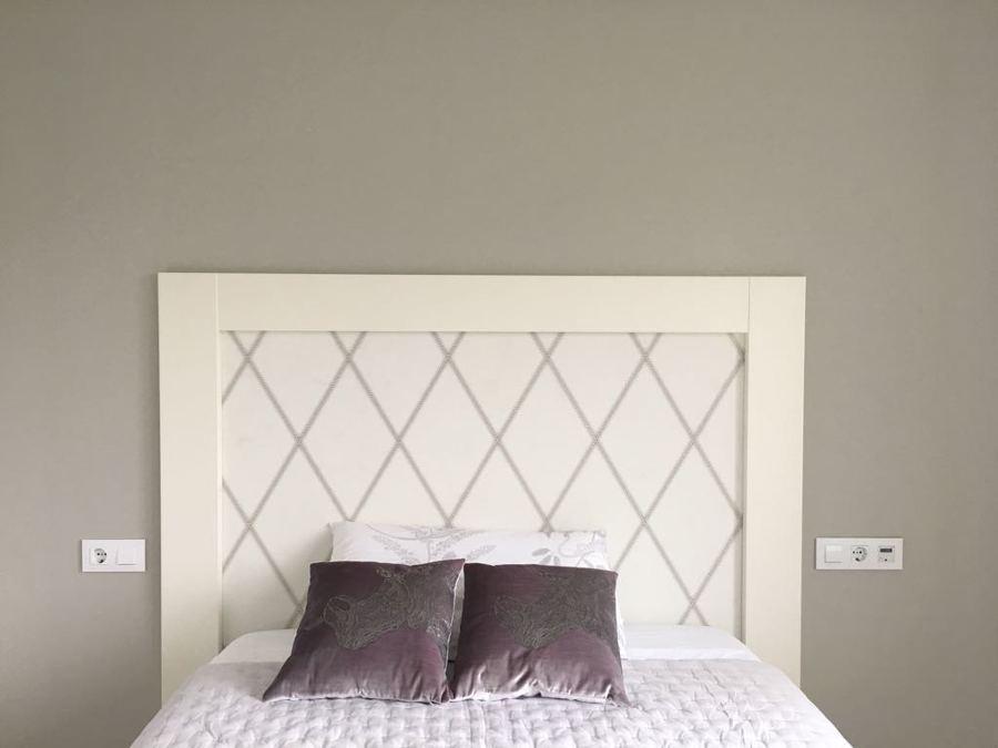 Cabecero, combinando texturas de madera y papel pintado, dando al espacio calidez y distinción.