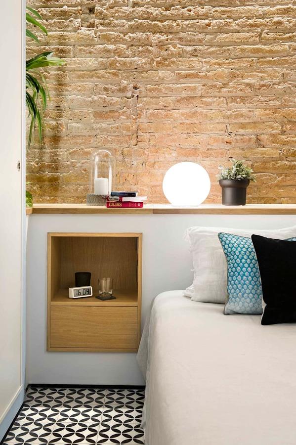 cabecero con muro a media altura, con pared de piedra y hornacinas forradas en madera