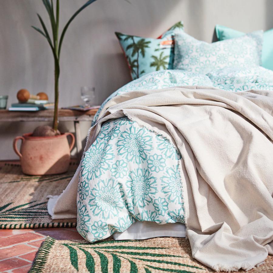 Cama con ropa de cama de algodón natural en tono azul claro
