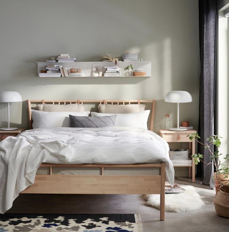 cama de madera con ropa de cama en color claro.