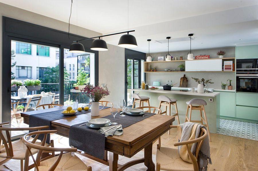 Cocina abierta al salón con gran mesa de comedor