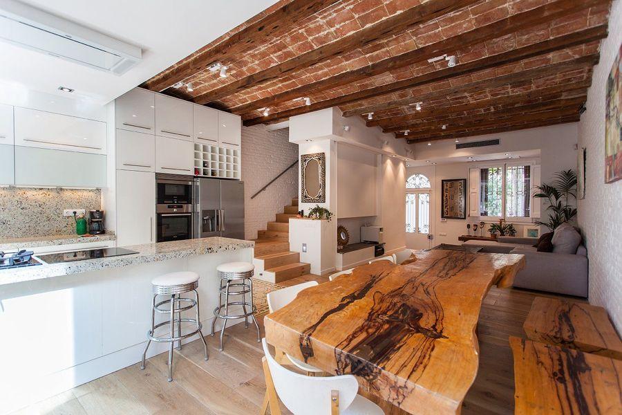 cocina abierta al salón con mármol y madera natural