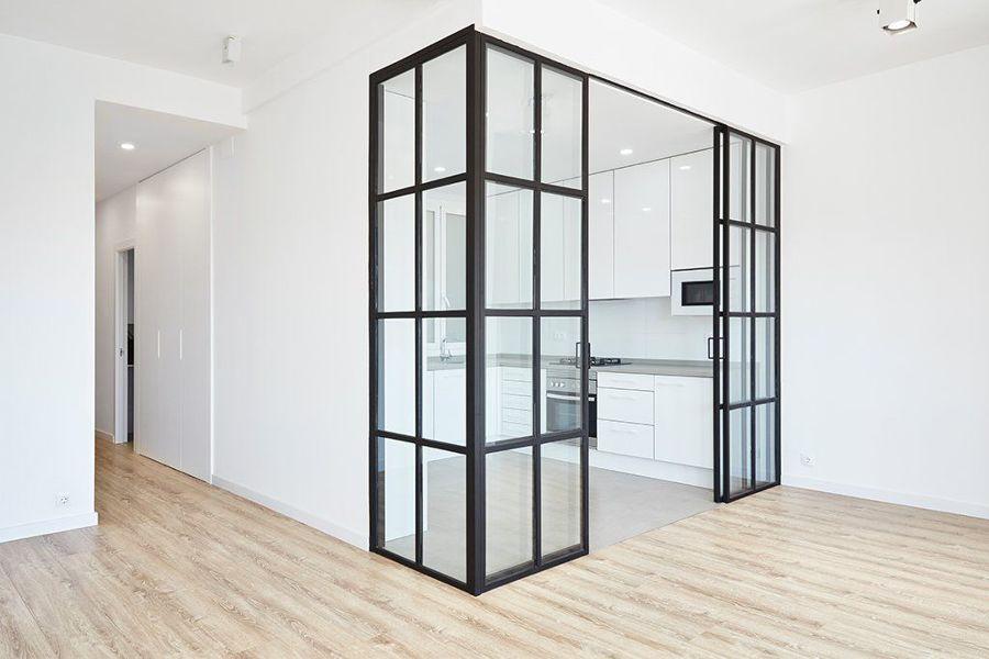 Cocina abierta al salón con muros de vidrio y metal