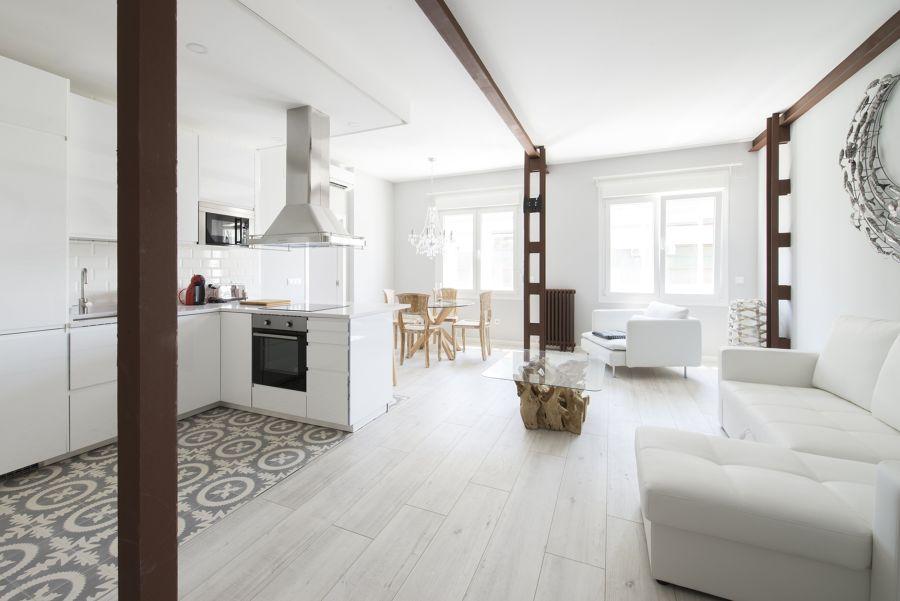 Cocina abierta al salón con vigas en marrón