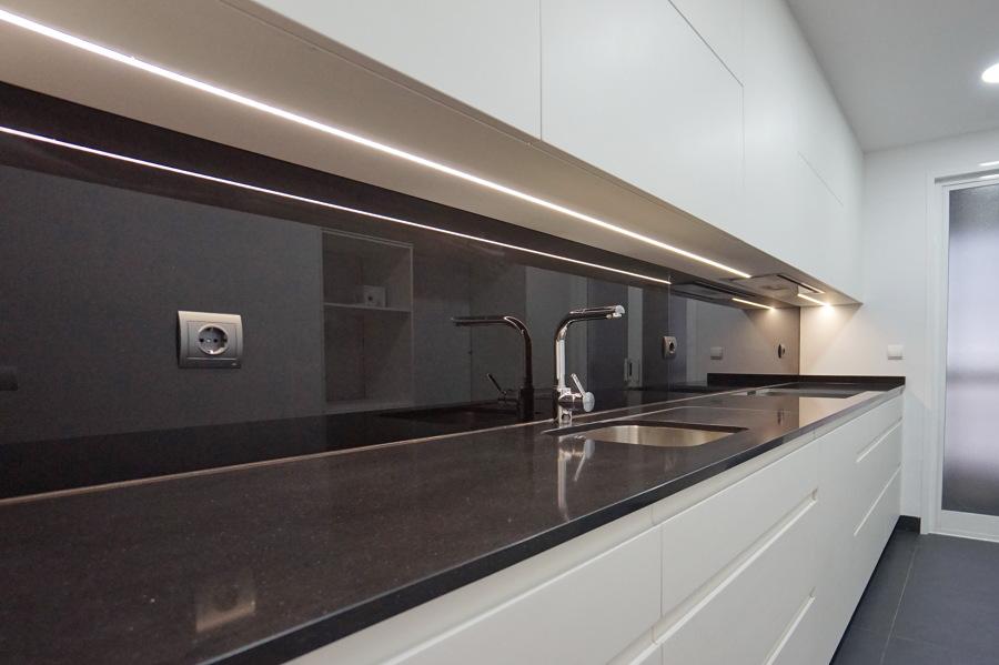 Cocina blanca con panel en vidrio negro