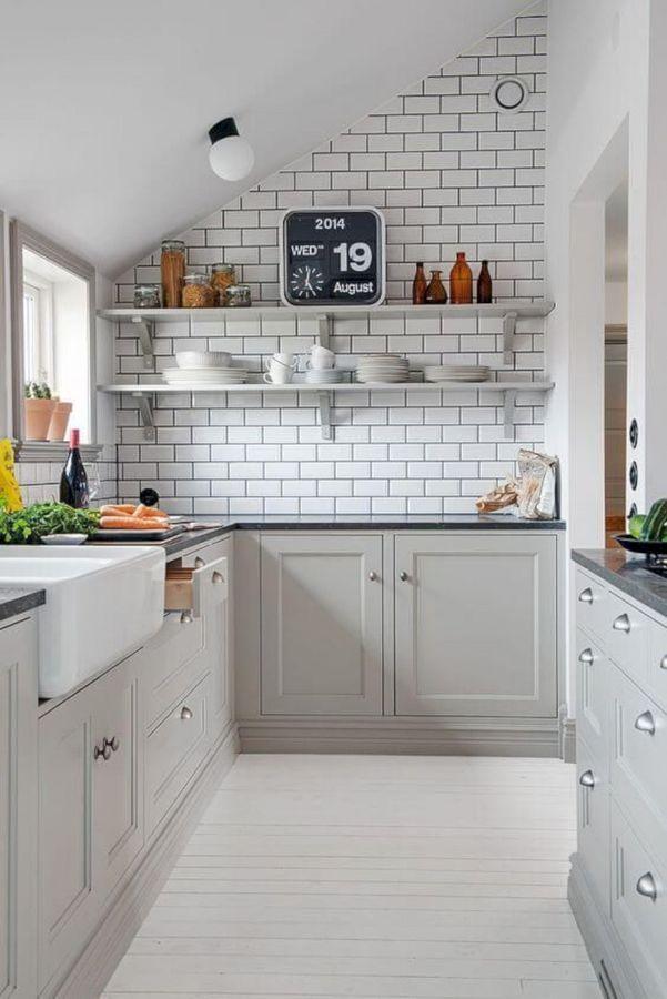 Cocina blanca con pared ladrillo vista y techo abuhardillado