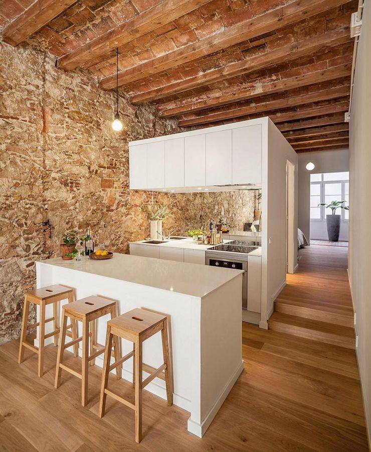 Cocina blanca con piedra y viga vista