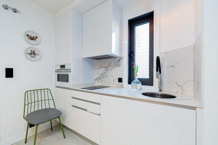 Cocina blanca moderna pequeña con encimera y frente de mármol