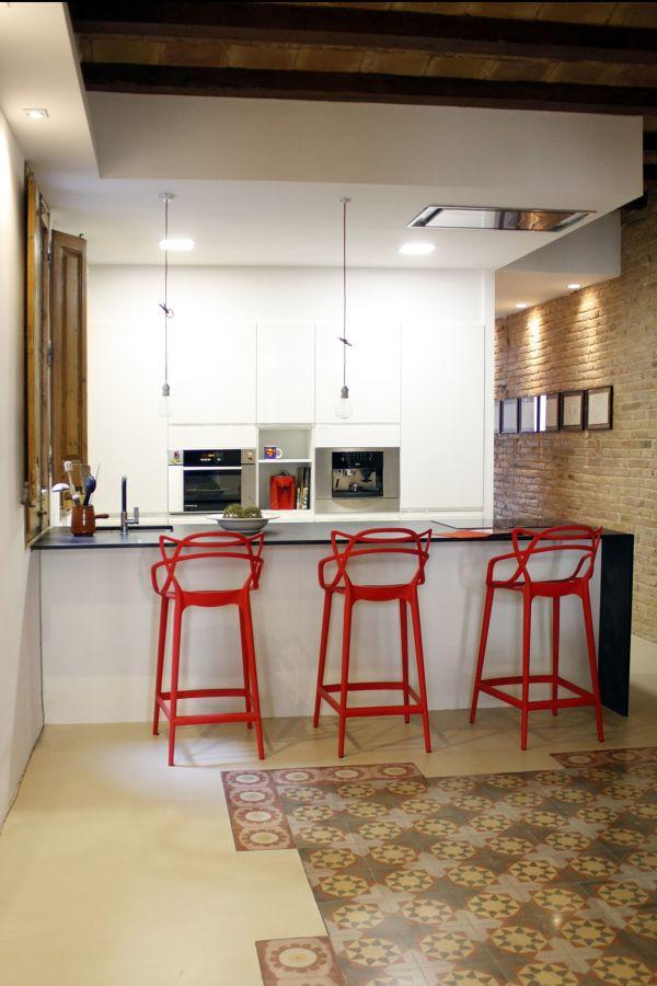 Cocina con barra negra y taburetes rojos