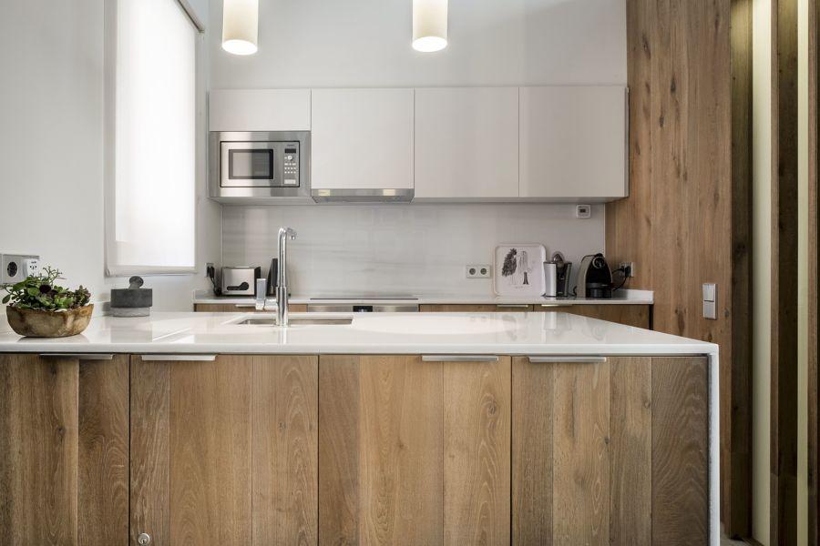 Cocina con gran península en color blanco y madera natural