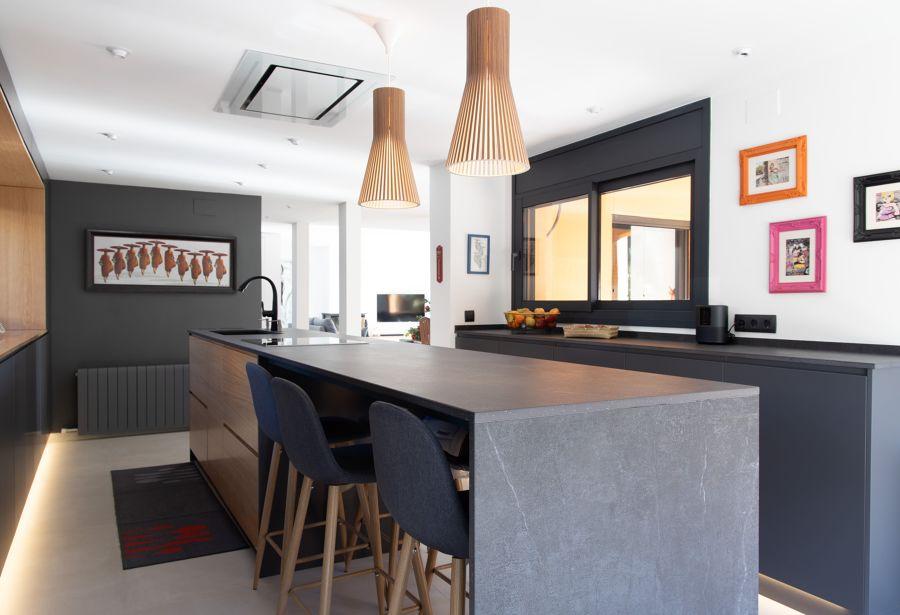 Cocina con isla de mármol negro y madera