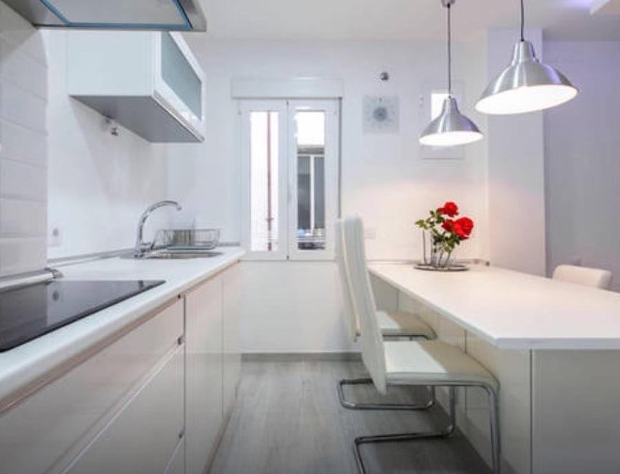 cocina, con mobiliario de almacenaje e isla que sirve de mesa de comedor