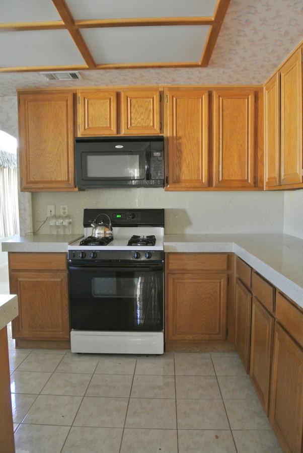 Cocina con muebles de madera y suelo cerámico