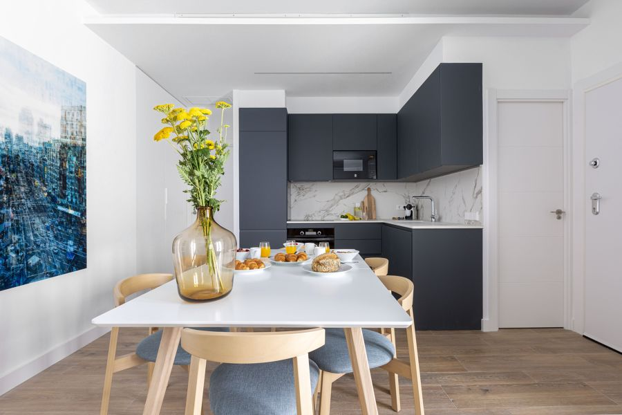 Cocina moderna abierta al salón con electrodomésticos integrados.