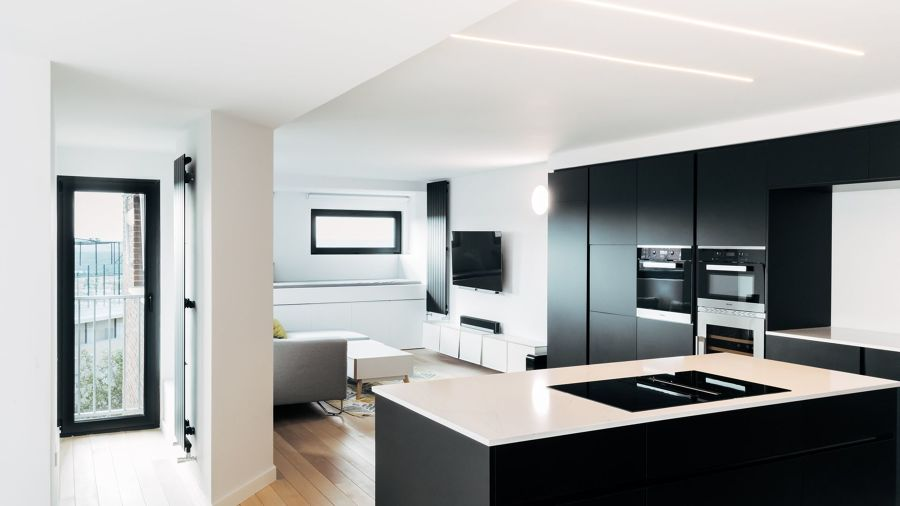 Cocina moderna abierta con frentes negros y encimera blanca