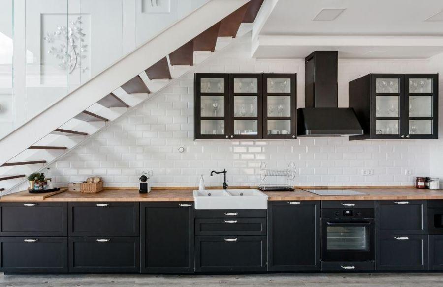 Cocina moderna con frente de madera negro y azulejo metro en el frente