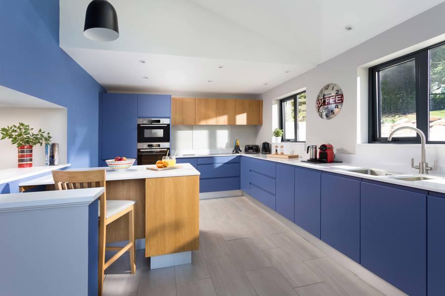 Cocina moderna con frentes en madera natural y color azul con encimera White Storm Silestone