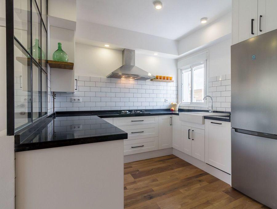 cocina moderna de planta abierta con azulejo tipo metro y porcelánico imitación madera en el suelo