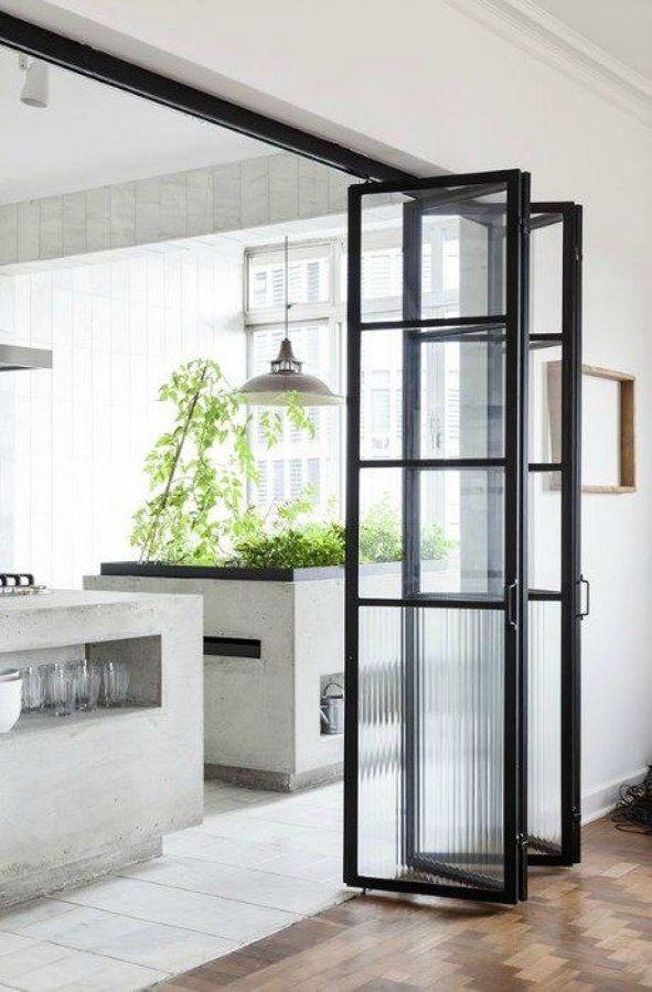 Cocina y salón unidos por puertas con perfilería en negro