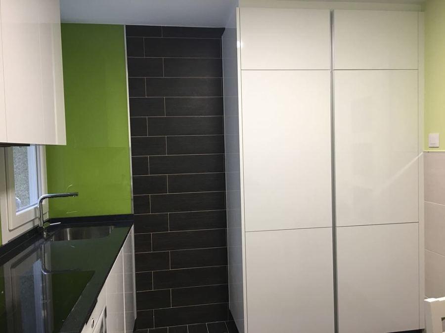 Combinación de texturas en pared, ocultando nevera y dando un amplio servicio de despensa.