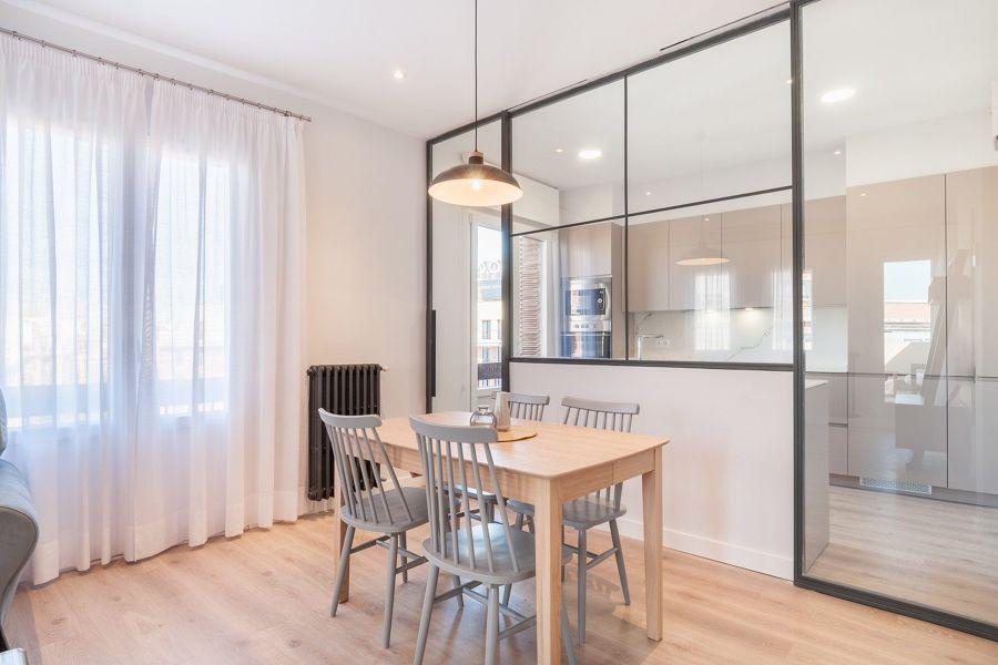 comedor abierto a la cocina con pared de cristal y calefacción con radiadores negros