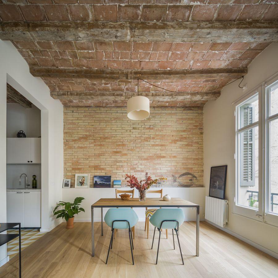Comedor con bovedillas descubiertas y ventanas de madera