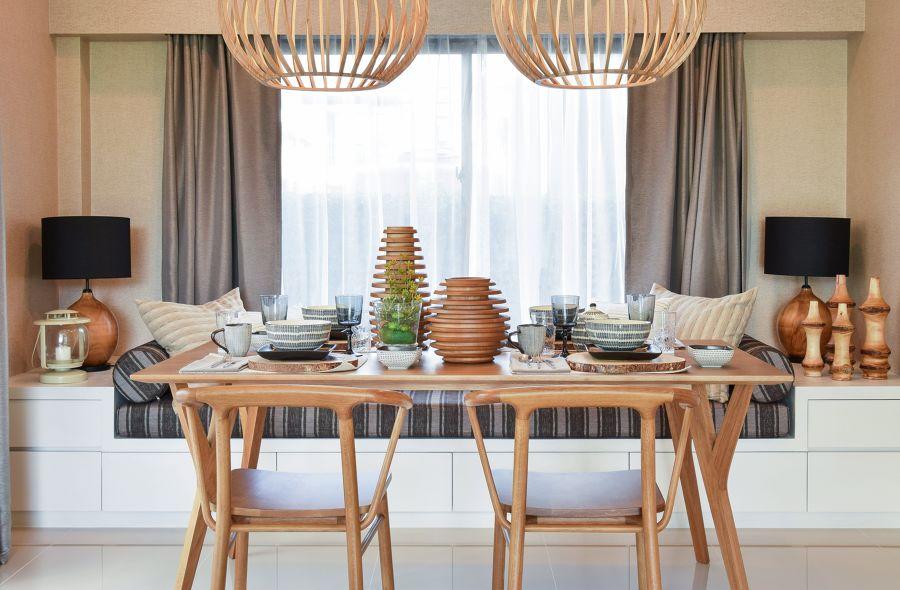 Comedor con gran mesa de madera y vajilla otoñal