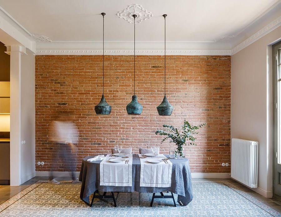 Comedor con pared ladrillo vista y lámparas