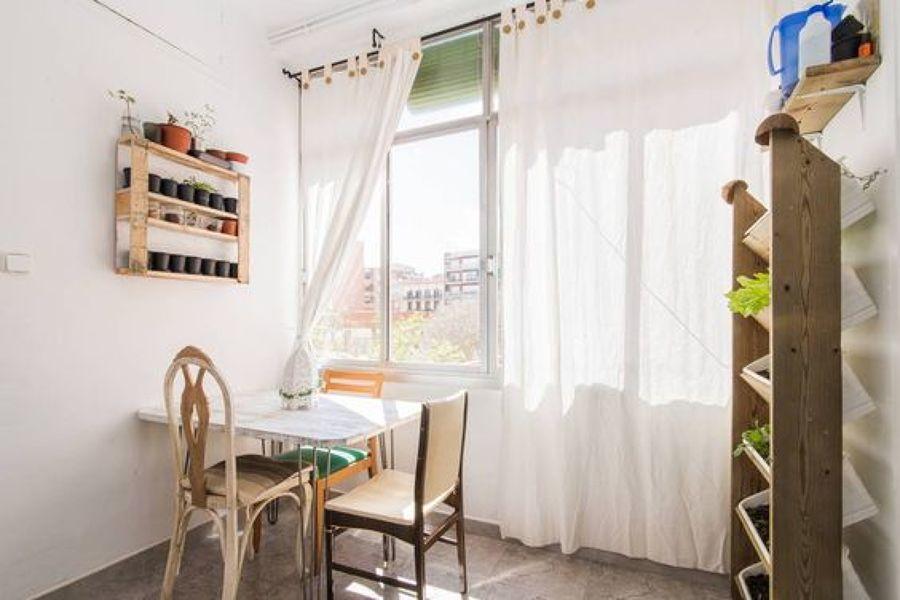Comedor con ventanal y huerto vertical