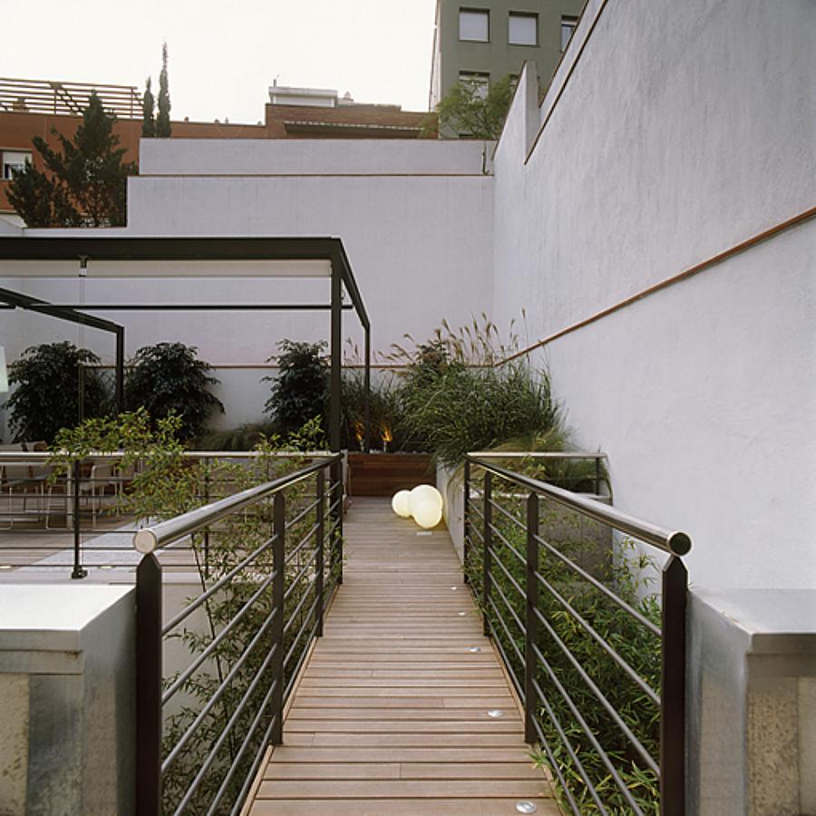 Conexión: Pasarela en madera Ipa conduce a la terraza superior desde la casa.