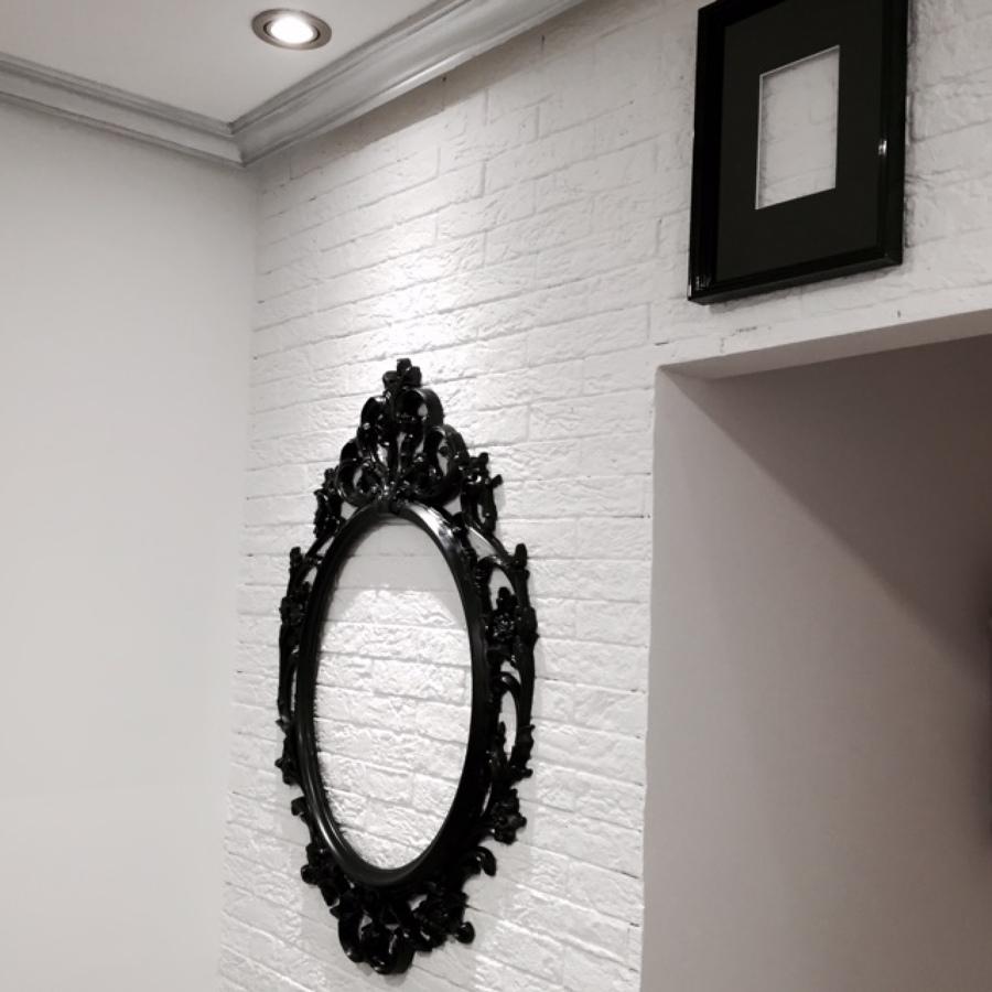"""Detalle pared revestida de ladrillo """"rústico"""", con marcos fotos colgados de ella"""
