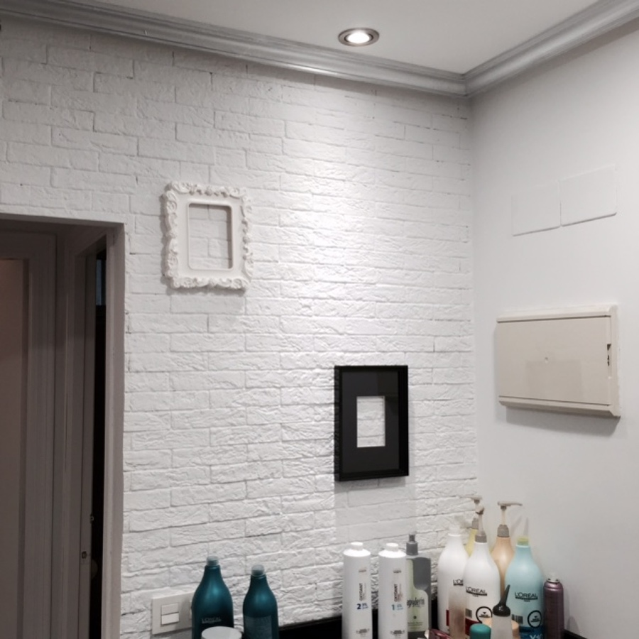 """Detalle pared revestida de plaqueta de ladrillo """"rústico"""", y moldura de escayola  pintada en plata"""
