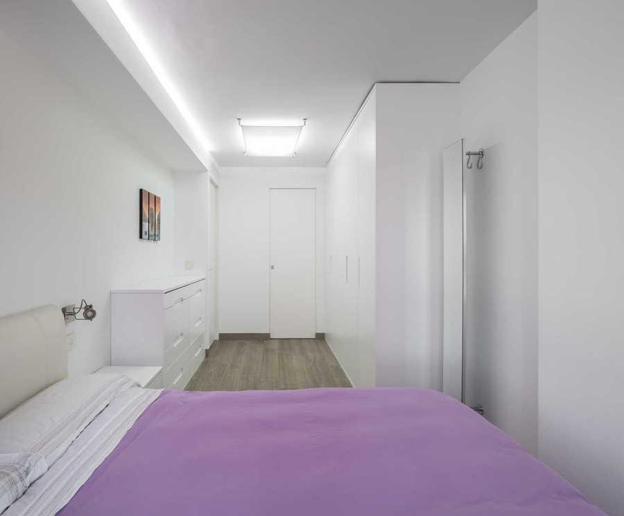 Dormitorio de color blanco con edredón malva