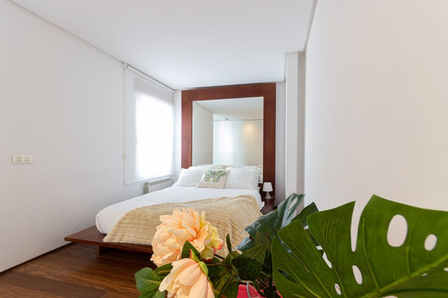 Dormitorio clásico con espejo en el cabecero