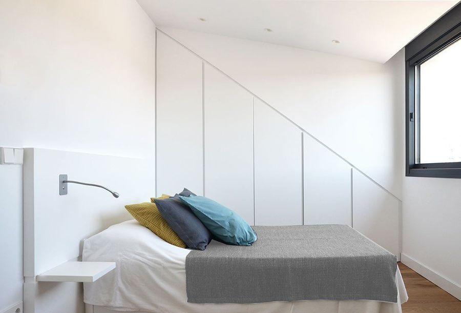 Dormitorio con armario empotrado en hueco de escalera