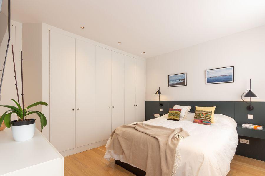 Dormitorio con armario empotrado y cabecero de madera a medida