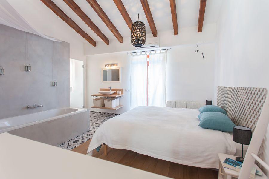 Dormitorio con bañera de microcemento