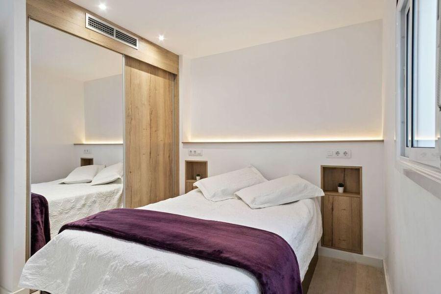 Dormitorio con cabecero de pladur y mesitas integradas, con armario empotrado con espejo