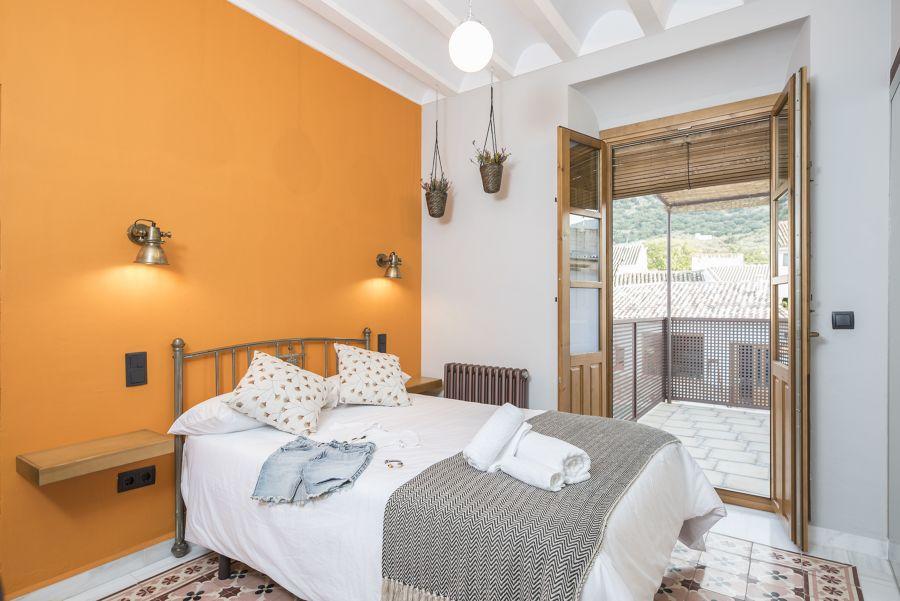 Dormitorio con cabecero pintado de amarillo ocre