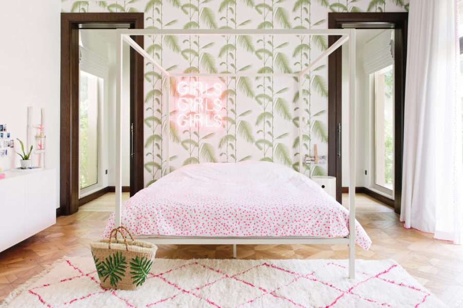 dormitorio con cama con dosel y papel pintado motivos tropicales